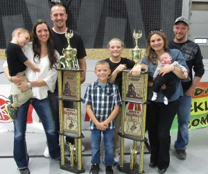 Trentyn is shown here with his trophies and his big family: brother Jaxen with mom Brooke, Step-dad Jeremy, sister Alyssa, Step-mom Sarah with brother Karson, and Dad Brent.