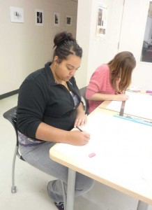MCC art student Fallon Carter works on a drawing during art class.