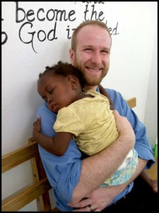 Josh Hunt holds a sleeping Jamaican child.