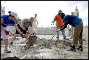 Team members help mix cement for addition.