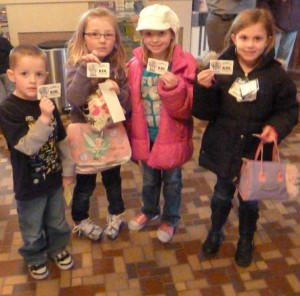 Four happy first graders show off their library cards at the Kent Theatre.