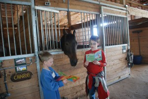Owen Secora, Shelby Dreyer, and Todd Stewart (volunteer) keep this horse entertained with a good book.
