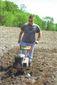 Dylan tills the soil.