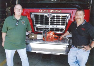 Fire Chief Marty Fraser and firefighter Brian Jenkins with the new saw.