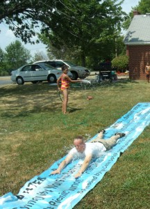 Pastor Jim practicing what he preaches and having fun with a water slide.