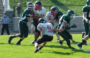 Keenan Gosselin (9), Connor Willits (14), and Demarcus Barnett (90) close in on the ball carrier from Wayland. Photo by Rebecca Klompstra.