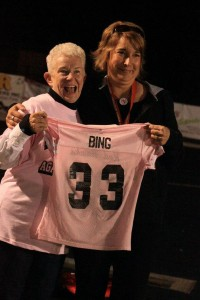 CS Athletic secretary Jen Myers (right) presents cancer survivor Alma Bing (left) with the jersey she wore during the Hawks Against Cancer pink game Friday night.