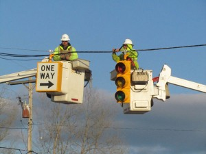Two MDOT workers put a new traffic signal on 17 Mile at the southbound US131 exit ramp. Post photo by J. Reed.