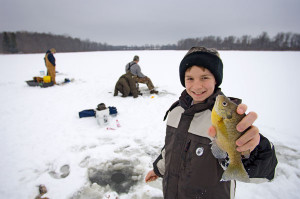 A young angler proudly shows off his recently caught bluegill while ice fishing in Michigan.