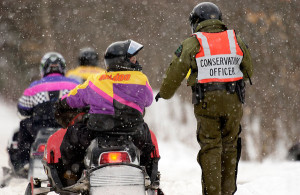 A Department of Natural Resources conservation officer checks in with riders while on snowmobile patrol in Alger County.