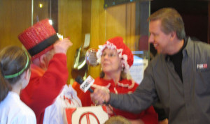 Kevin Craig interviews both Rose Powell (right wearing granny cap) and her mother-in-law Alice Powell (left wearing top hat) about their Red flannel wear.