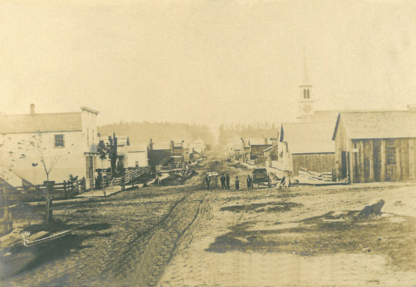The photo shows the village of Cedar Springs from the corner of Main and Muskegon Streets, looking north, about 1871, the year it was officially incorporated as a village by the state legislature. According to the Cedar Springs Story, the white frame building on the left was Black's first store, and on the right is O'Dell's Blacksmith shop, with his wagon shop just north of that. Rising behind them is the spire of the Methodist church, which was built in 1871. This photo was on a 1907 postcard, which said it was Cedar Springs, about 30 years ago.
