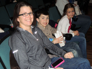 Torie Sherburn (mom), first-grader Jack Sherburn and Lauren Sherburn enjoying the celebration at the Kent Theatre. The movie was shown free to first graders on Monday, March 4 and Tuesday, March 5. Photo by Shannon Vanderhyde.