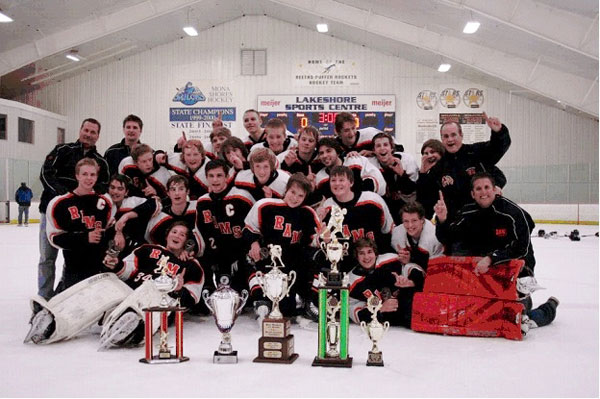 2012-2013 Rams JV Hockey team celebrates after winning their season-ending league tournament.  Along with their impressive collection of championship trophies won throughout the '12-13 season.  Team members include: Chris Anderson, Ian Bach, Bradley Barnard, Joey Bazaire, Christian Conati, Will Fisher, Jacob Harkema, Ryan Harpst, Damon Harvey, Cam Hendrie, Collin Hooper, Alan Kolenda, Jacob Moroney, Nick Peterson, Sam Price, Colin Rebhun, Jordan Taylor, Jarrett Ullrey, Austin Winicki Coaching staff includes:  Head Coach, Chris Davis; Assistant Coaches,  Gord Angus, John Lapham, Emery Lovse; and Team Manager,  Mike Bazaire.  Above: Tournament action. Left: Rams Head Coach Chris Davis (far right) with the WMJVHL Year End Tournament Cup and players (from left to right, Jake Harkema, Jarrett Ullrey, and Austin Winicki).