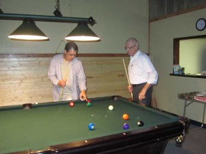 Alex Schreer teaches Mayor Bob Truesdale about pool.