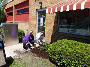 Two Garden Club members, Christine McFarlane (left) and Caroline Bartlette (right), are shown here landscaping in front of the Cedar Springs Public Library.