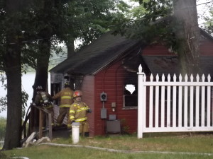 Firefighters work to make sure the fire is out on this Maston Lake home. Post photo by J. Reed.