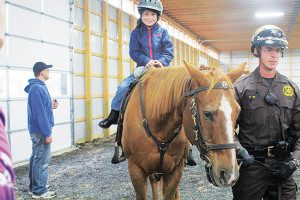 Kids were all smiles while sheriff deputies help them ride around the new arena for the Kent County Sheriff's Mounted Division during a grand opening last week. Photo by B. Altena.