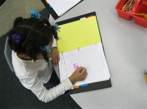 Second grade student Timiah DenBoer graphing her reading levels in her data binder.