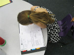 Second grade student Analiese VanHarten graphing her math assessment in her data binder.