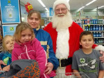 The Goltz family poses for a picture with Santa at Family Fare