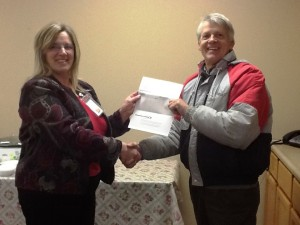 Daniel Clark, receiving check from Dru Ross, representative from Consumers Energy