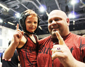 Coach Dave Andrus and Blake Peasley stepping off the mat after an undefeated season and becoming a 2014 State Champion.