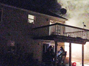 Above shows smoke rolling out the upstairs slider door during the fire, as firefighters work to extinquish the flames in the basement. Post photo by B. Sanderson