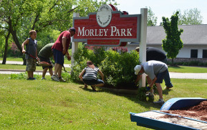 Members of The Springs and Solon Center Wesleyan worked together on many projects Sunday, including planting flowers and weeding around signs.