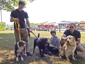 (L to R) Hanco, Raymond, and Hannes Smit helping with dogs during the fire at the kennel. Post photo by J. Reed.