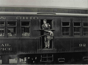 Post office clerk in a mail car ready to make an outgoing-incoming mail exchange.  Photo courtesy of Cedar Springs Historical Society.