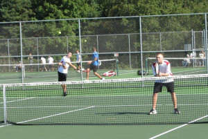 Doubles team Jon Baculy serving the ball and Ethan Brown ready for a return from the opposing team.
