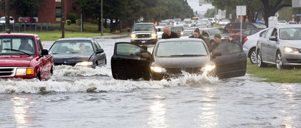 Motorists help push stalled vehicles at Tidewater Drive and Virginia  Beach Boulevard in Norfolk on Monday, Sept. 8. Patrick French, of Cedar Springs, second from the left, married Erica (Placers) French earlier, and the two spent their afternoon helping motorists stalled in the floodwaters. (The' N. Pham|The Virginian Pilot)
