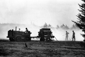 Historical photo depicts a pull-behind water unit connected to hand lines for fire suppression.