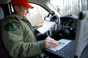 Conservation Officer Terry Short uses a plat map to cross-reference information he receives from the RAP (Report All Poaching) Line dispatchers while on patrol during deer season in Menominee County.