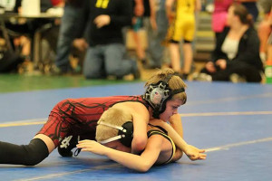 Logan Bennet, from the 9/10 Novice age group, wrestles an opponent.