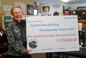 An anonymous donation of $170,000 was made to the Community Building Development Team. Treasurer Betty Truesdale holds a sign announcing the donation.