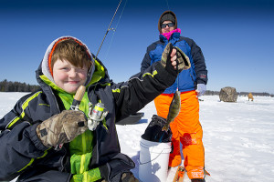 Kyle Draper shows off a yellow perch (that he caught at an ice-fishing clinic at the DNR's Carl T. Johnson Hunting and Fishing Center) to his mom, Angie. 