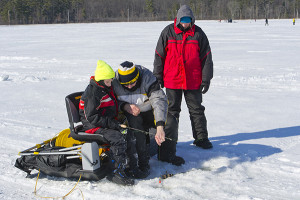 A volunteer instructor shops a young angler how to use a weight at an ice-fishing clinic at the DNR's Carl T. Johnson Hunting and Fishing Center. Michigan DNR photo.