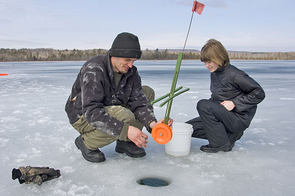 The spool that holds the line on a tip-up is submerged below the ice to keep it from freezing.