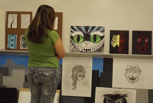 A visitor to Community Night 2014 admires a Cheshire Cat created by a Cedar Springs student. Community Night is a chance to try out something new and meet the people who live, work and play in our community. Post photos by J. Reed.