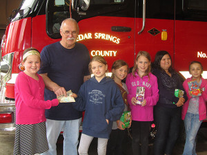Cedar Springs Fire Chief Marty Fraser accepts donation from Brownie troop #4282. Photo by J. Reed.