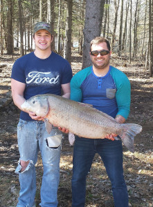 Black Buffalo Record: Sage Colegrove (right) holds on to his new state-record black buffalo, with help from friend Richard Laing (left). The 44.54-pounder was caught on the Grand River in Ottawa County.