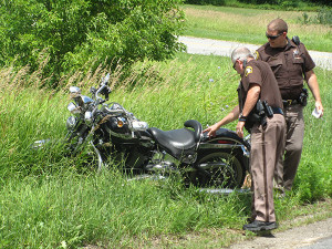 Kent County Sheriff Deputy Ron Kimbrough and Deputy Scott Abbatoy look at the motorcycle involved in the accident Monday. Post photo by J. Reed.