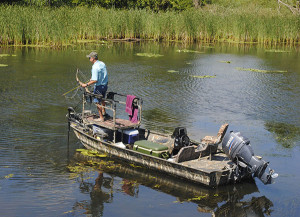 Roy Beasley, DNR Fisheries Division, surveys the shallows from an elevated platform on his boat at Lake Erie. Michigan DNR Photo.