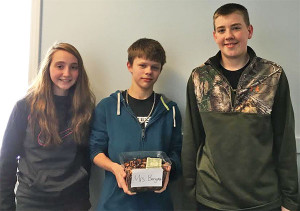 8th grade students Zoe Lehman, Cameron Almy and Luke Hubbard with one of the filled coin war tubs.