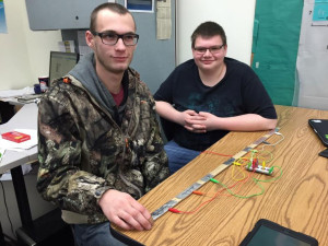 Seniors Keegan Shears (L) and Josh Davidson (R) with their Pong game controller made out of a yard stick and circuits.