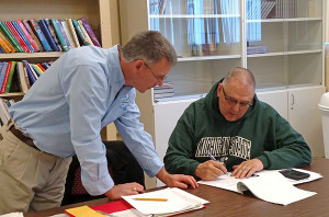 Kurt Mabie (right), Chair of the Community Building Development Team, signs the document for the National Country Trail to come through our area. Christopher Loudenslager from the National Park Service is on the left.