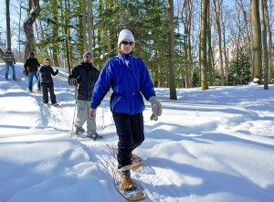 A group snowshoes through a northern woodland, enjoying a sunny Pure Michigan winter's day.
