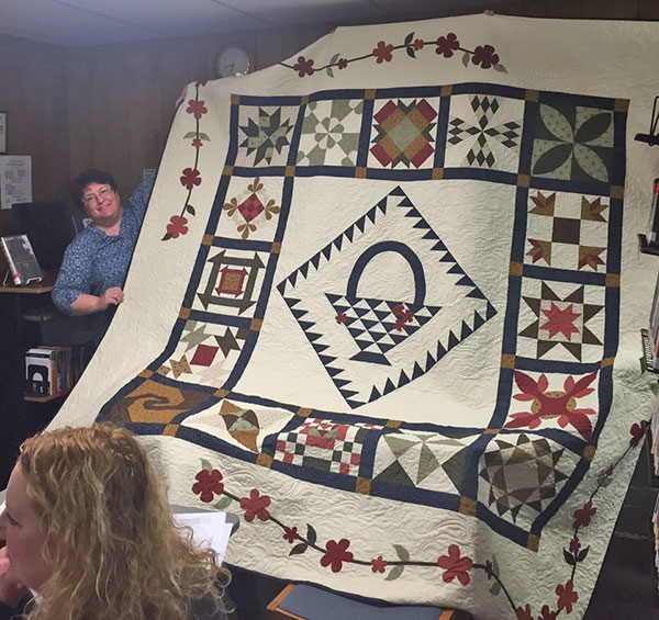 This quilt, shown by Barb Grutter, will be raffled off at the Cedar Springs Friends of the Library quilt show on March 19. Get your tickets at the library.